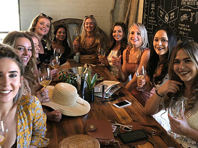 a bunch of lady tourist having so much fun while enjoying the place and the taste of their wine in their pokolbin wine tours